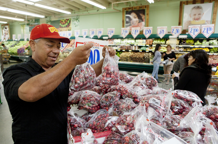 Customer Prieto Valenzuela shops for seasonal cherries at a Superior Grocers store in Los Angeles recently.