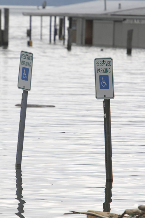 Signs are under water in a flooded parking lot today in Burlington, Vt. Already swollen to a record level, Lake Champlain continues to rise, prompting a handful of evacuations and sandbagging of low-lying homes along the Vermont and New York shore.