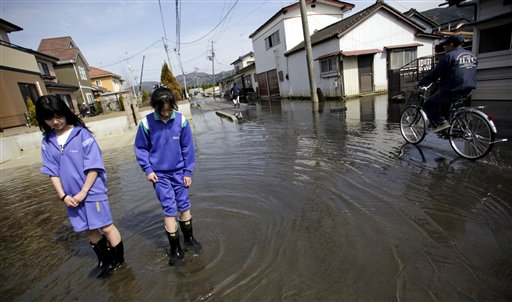 In this May 3, 2011, photo, Itsuki Mogi, 11, left, and and Umi Mogi, 12, watch the moving sea water in a street in front of their house in Ishinomaki, Miyagi Prefecture, Japan. The area in this part of the city sunk nearly 2 feet 7 inches (0.8 meter) following the March 11 earthquake and tsunami.
