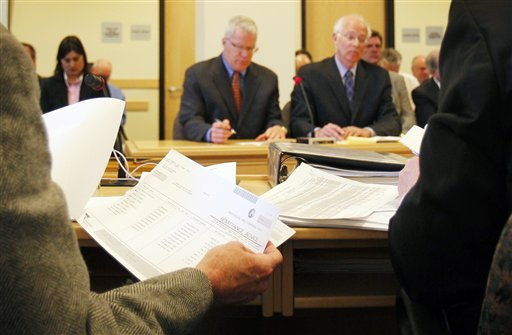 A member of the Legislature's Government Oversight Committee, reviews spending records during the questioning of Paul Violette, the former executive director of the Maine Turnpike Authority, Friday, April 15, 2011, in Augusta, Maine. Violette, in background at left, invoked his constitutional right against self-incrimination and refused to answer questions about the authority's spending practices. (AP Photo/Robert F. Bukaty)