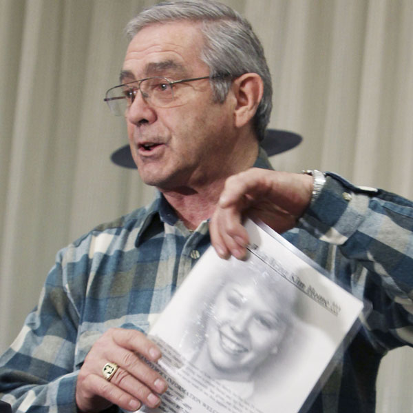 Dick Moreau speaks at a news conference today with a photograph of his daughter Kim.