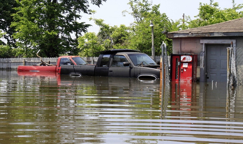 Floodwater surrounds two pickup trucks outside a garage in Memphis, Tenn.