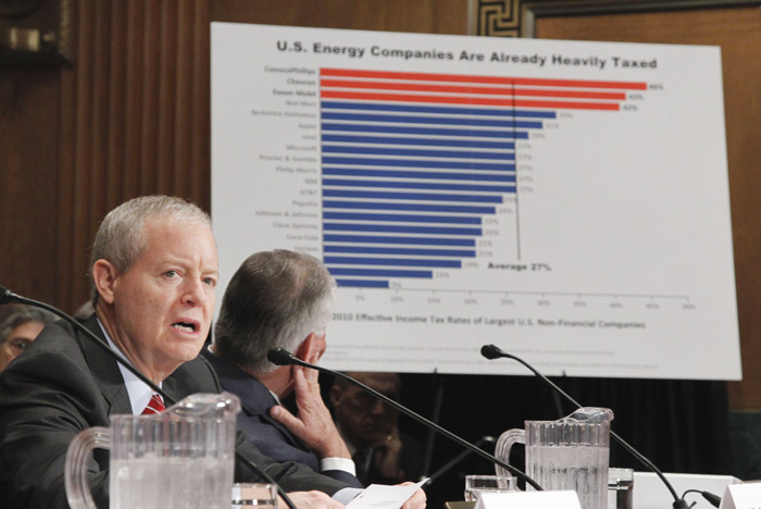 ConocoPhillips CEO James Mulva, left, speaks while ExxonMobil CEO Rex Tillerson looks at a chart on Capitol Hill today.