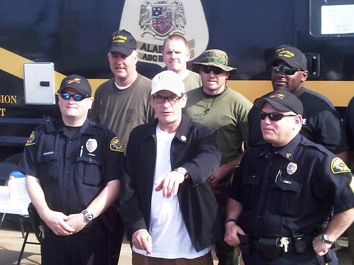 Actor Charlie Sheen poses with police officers and National Guard soldiers today in Tuscaloosa, Ala.