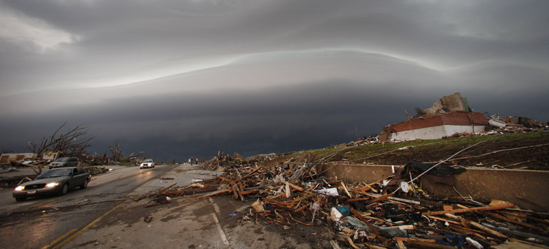 A shelf cloud containing a thunderstorm approaches a tornado-ravaged neighborhood in Joplin, Mo., today, where a large tornado moved through much of the city Sunday, damaging a hospital, hundreds of homes and businesses and killing at least 89 people.