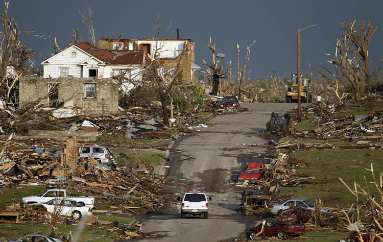 An emergency vehicle drives through a severely damaged neighborhood in Joplin, Mo., today.