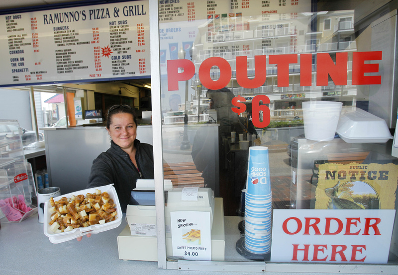Karen Ramunno of Ramunno's Pizza and Grill, delivers an order of poutine, a french fry, gravy and cheese dish popular with Canadians, at Old Orchard Beach. With the summer tourism upon New England, merchants, hotel operators and restaurateurs have pinned high hopes on the strong Canadian dollar luring plenty of tourists from north of the border.