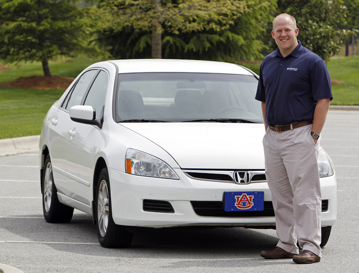 Jeremy Barnes poses recently in front of the 2007 Honda he is selling near his home in Greensboro, N.C. With used-car prices at 16-year highs, and a child on the way for him and his wife, Barnes is hoping to sell it for a good price and most likely spend more on the new car they buy.