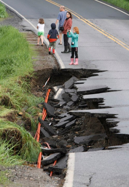 Residents look over a damaged road today in East Montpelier, Vt.