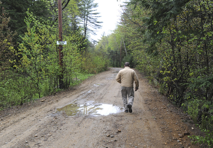 A member of the South Berwick Police Deptartment walks down a dirt road at 100 Dennett Road in South Berwick where the body of a young boy was found on Saturday.