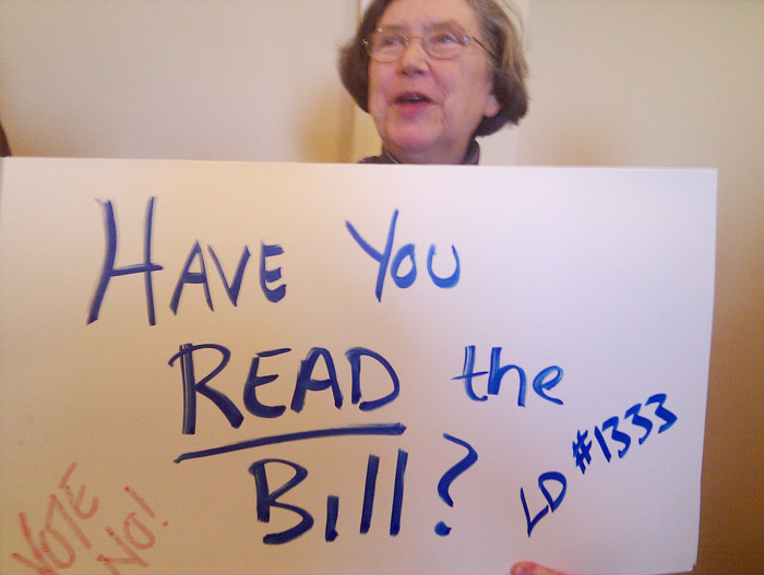 A protester greets legislators at the State House today.