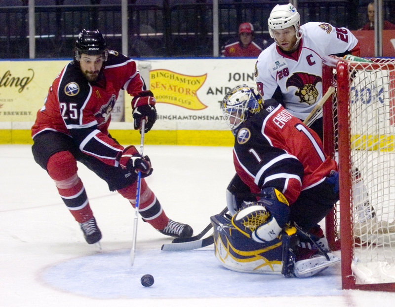 Mark Mancari, left, of the Pirates moves in to take possession of a blocked shot by goalie Jhonas Enroth as Binghamton's Ryan Keller waits for the rebound tonight in Binghamton, N.Y. The Pirates won 6-2 to stay alive in the series, which returns to Portland Friday night.