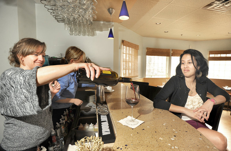 Zeus-Hannah Suzette pours a glass of red wine as Bianca Gonzalez watches at Azure Cafe on Main Street in Freeport. The cafe is well known for its wine selection, but also offers locally brewed beers and creative cocktails.