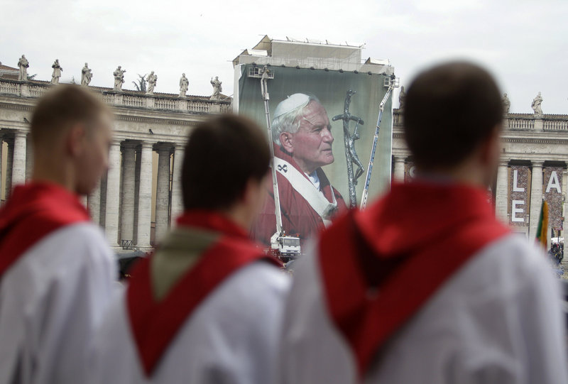 A Polish choir sings in front of a giant photo of Pope John Paul II at the Vatican Saturday, a day before his beatification.