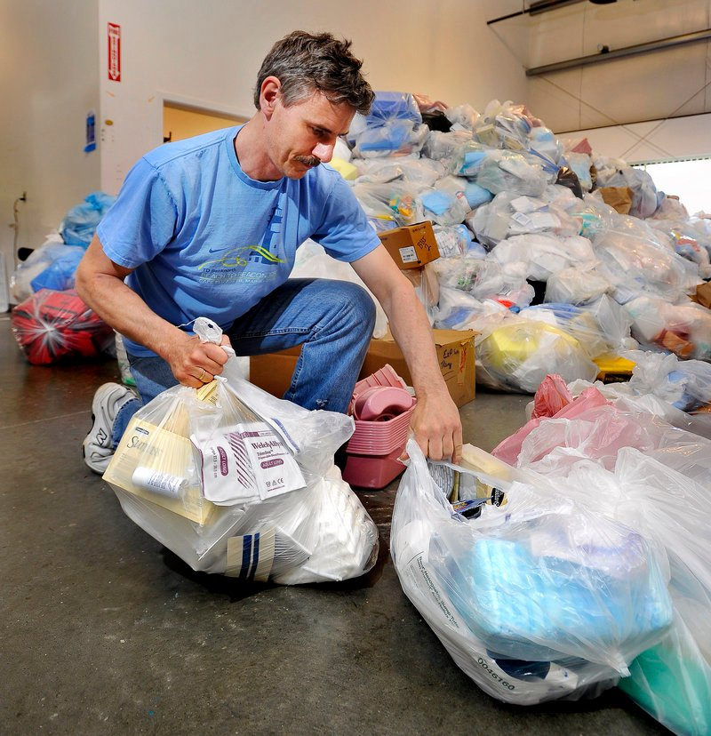 Volunteer Uwe Kirchner sorts donated items recycled from hospital rooms for packing.