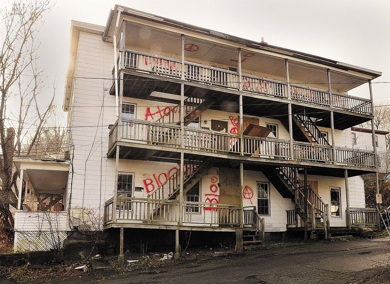 """This abandoned apartment building at 6 Morton Place in Augusta is covered with asbestos shingles, and """"there is literally eight to 10 inches of debris on the floor, on every floor,"""" says Bob LaBreck, the city's facilities manager."""