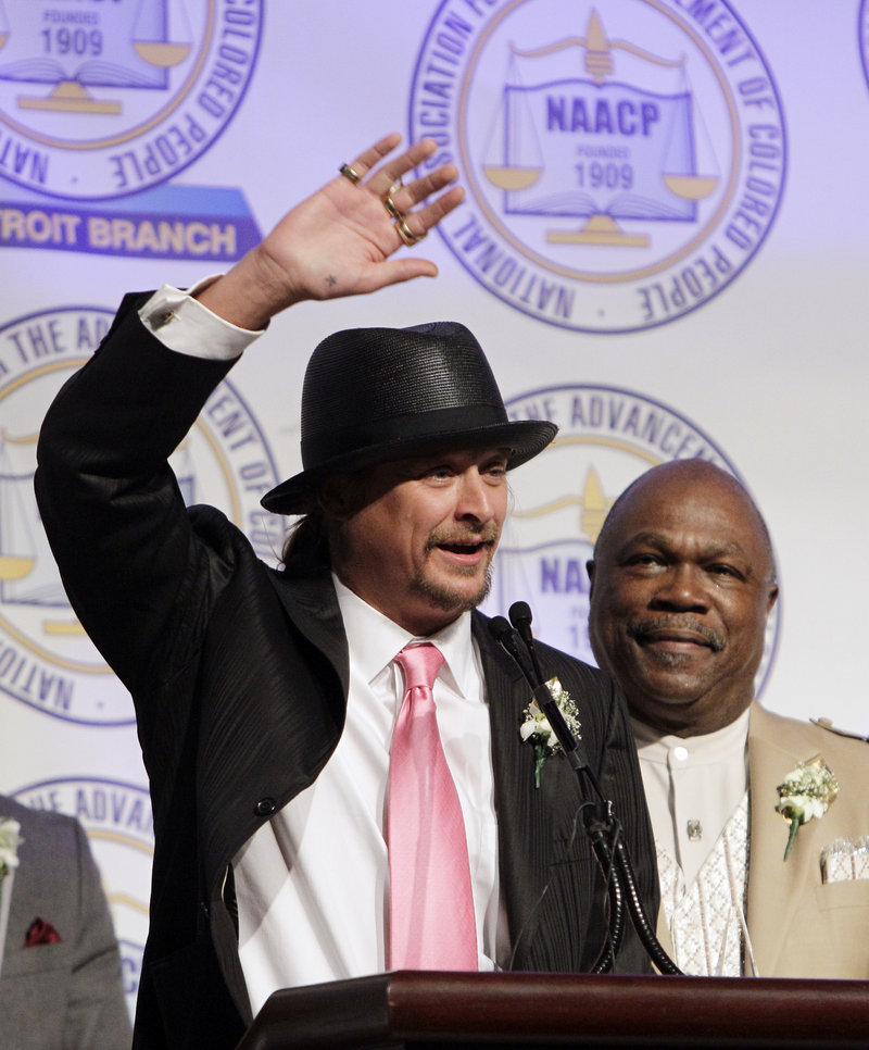 Kid Rock, standing next to NAACP Detroit Chapter President Wendell Anthony, acknowledges the audience during the organization's annual fundraising dinner in Detroit on Sunday.