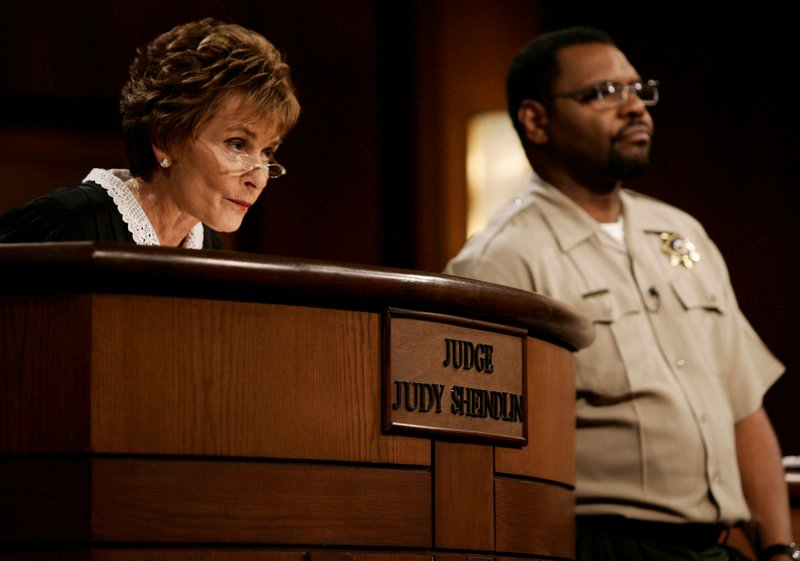 """Judge Judy Sheindlin presides over a case as her bailiff Petri Hawkins Byrd listens on the set of her show """"Judge Judy."""" She had toyed with the idea of ending the show in 2013 but signed a deal that was announced Monday."""
