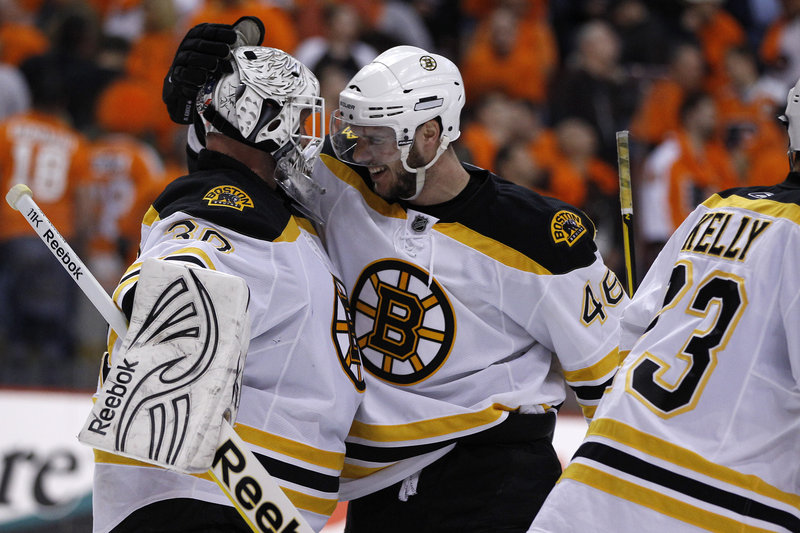 Tim Thomas, left, is congratulated by David Krejci after the Bruins beat the Flyers 3-2 on Monday. Thomas made 52 saves.