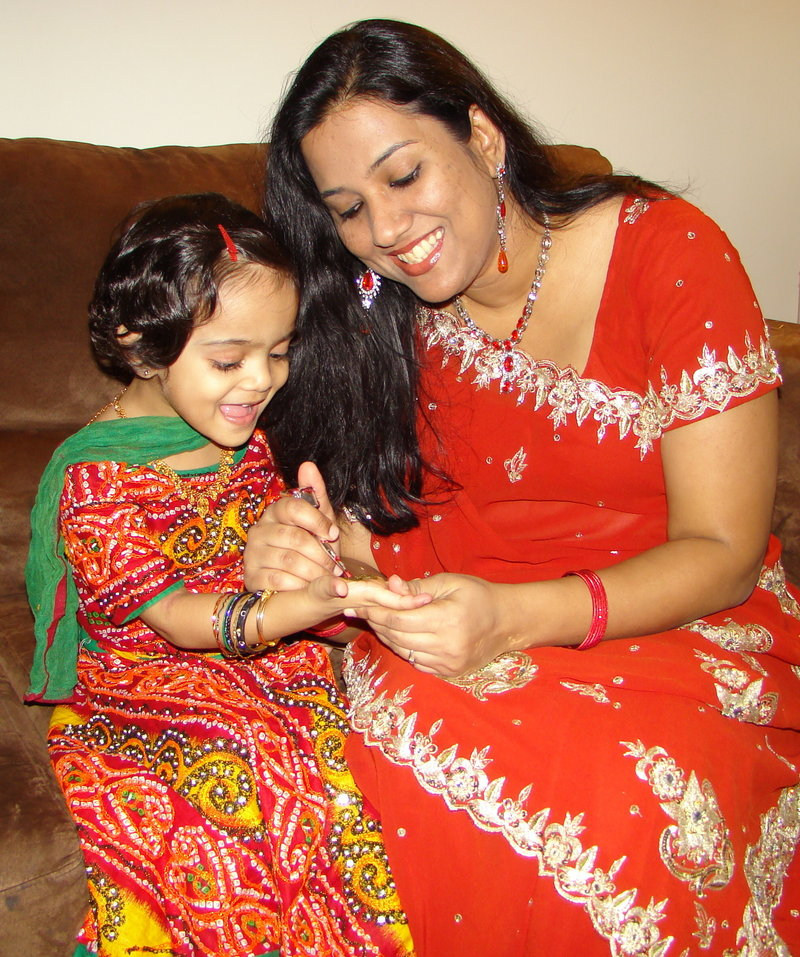 Sabina Naik paints henna onto her daughter Sarah Girach's hand. Hand painting and bindi forehead painting will be offered during the festival.