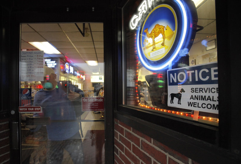 A sign welcoming service animals appears in a window of Sonny's Variety Store in Portland. The store's owner, Peter Brichetto, Jr., put the sign there as part of a criminal charge settlement.