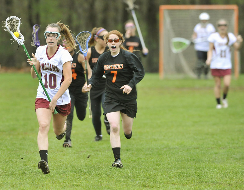 Michelle Giroux of Thornton Academy races down the field Wednesday after coming up with a ground ball during the 15-1 victory against Biddeford in a schoolgirl lacrosse game at Saco. Danielle MacDonald of the Tigers gives chase. The Golden Trojans improved their record to 3-1. Biddeford is 0-3.