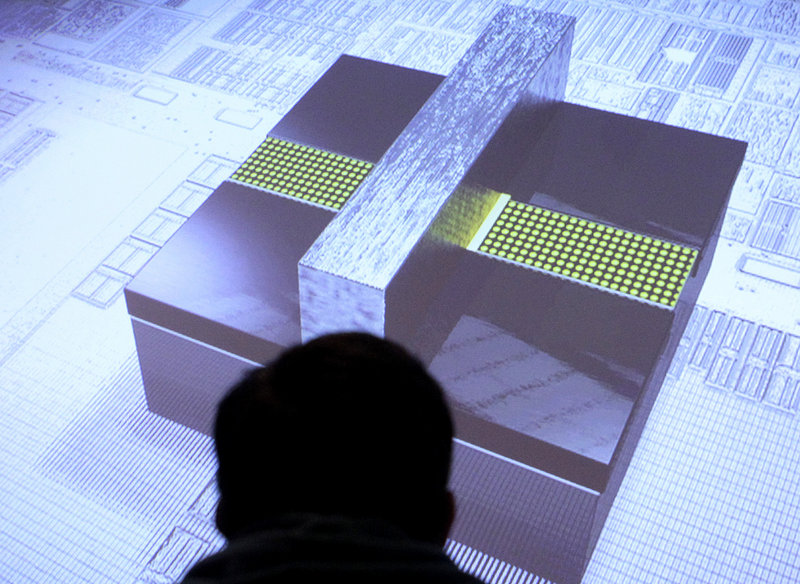 """A reporter watches an image of a 3-D """"tri-gate"""" transistor after it was unveiled in San Francisco last week."""