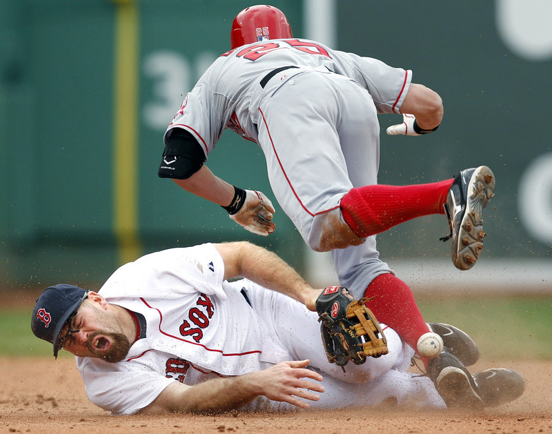 Kevin Youkilis of the Red Sox lies on the ground after colliding Thursday with Peter Bourjos of the Los Angeles Angels, who singled and moved to second when the base was uncovered. Youkilis had raced over to cover. Bourjos continued on to third.