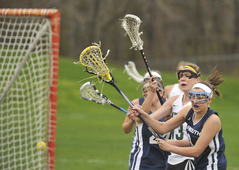 Sadie Cole of Waynflete finds room between Danielle Torres, left, and Clare King of Yarmouth for one of her five goals Thursday in an 11-10 victory for the Flyers, who sent the Clippers to their first girls' lacrosse loss of the season.
