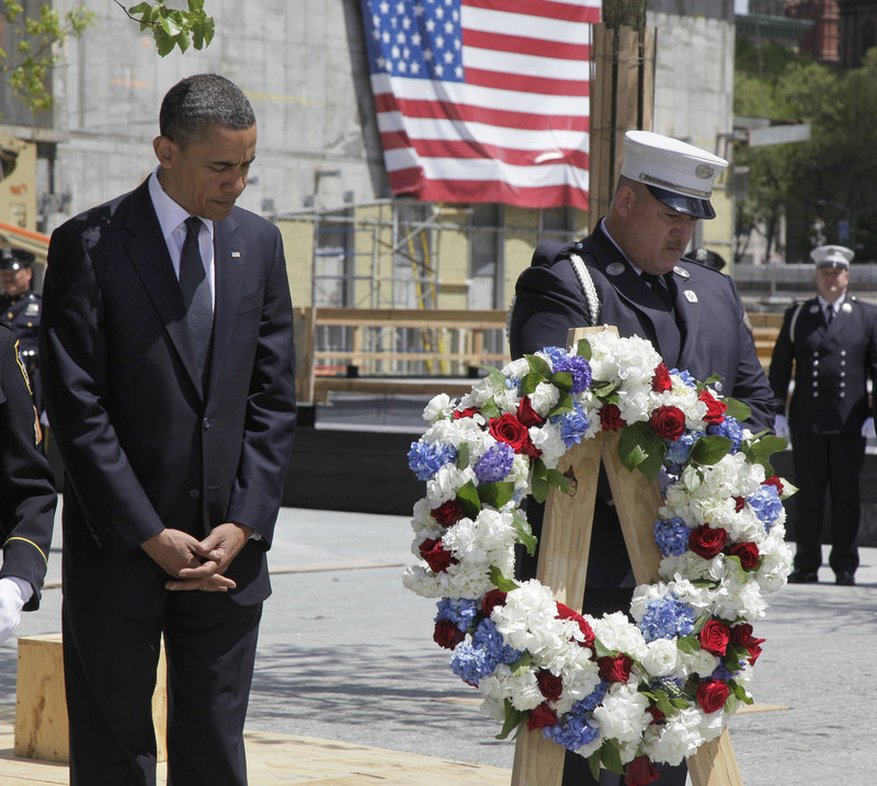 President Obama, accompanied by a New York City firefighter, observes a moment of silence Thursday at the site of the World Trade Center towers. He did not make any public remarks but spoke privately to a group of firefighters.