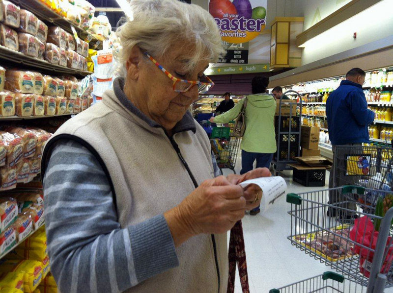 Vicenza Cerrato, 83, of North Wales, Pa., looks at a grocery receipt at a Giant supermarket as she compares prices with those of discounter Bottom Dollar Food.