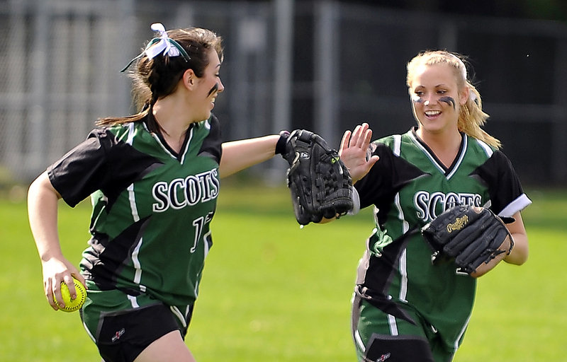 Left fielder Julia Boucher of Bonny Eagle receives a high-five from center fielder Brittany Murphy after catching a deep drive to end an inning Friday. Murphy had two hits to help the Scots to a 12-3 victory against Windham in an SMAA softball game at Standish.