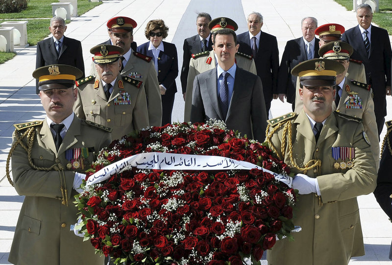 Syrian President Bashar Assad, center in blue tie, arrives to lay a wreath at the tomb of the unknown soldier during Martyr's Day in Damascus on Friday. Syrian anti-regime protesters again took to the streets across the country on Friday; dozens were slain by security forces.