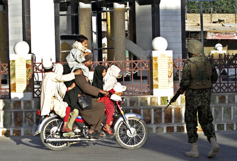 An Afghan security officer checks a bike carrying seven passengers after gunmen launched an attack on the governor' s compound in Kandahar province, south of Kabul, Afghanistan, on Saturday.