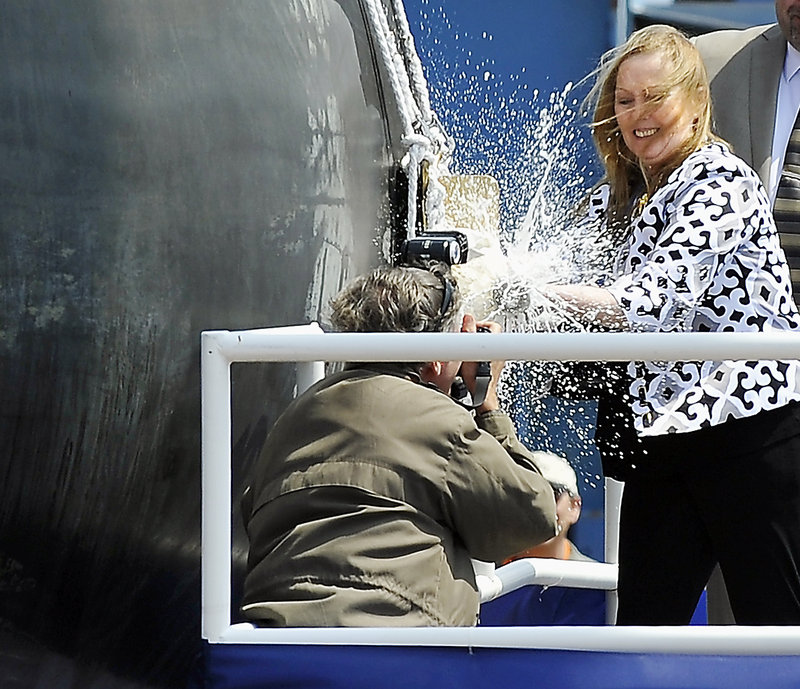 """Maureen Murphy, the ship's sponsor and mother of Lt. Michael Murphy, christens the Michael Murphy (DDG 112) with a bottle of champagne Saturday at Bath Iron Works. """"I wanted to do a good job. I just wanted to do it right,"""" she said."""