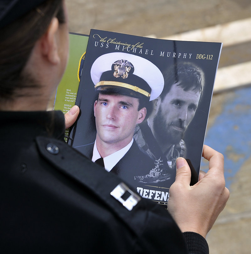 """A Navy officer reads the christening program, adorned with images of Lt. Michael Murphy, who is featured in the book """"Lone Survivor"""" by Petty Officer Marcus Luttrell, also a Navy SEAL."""