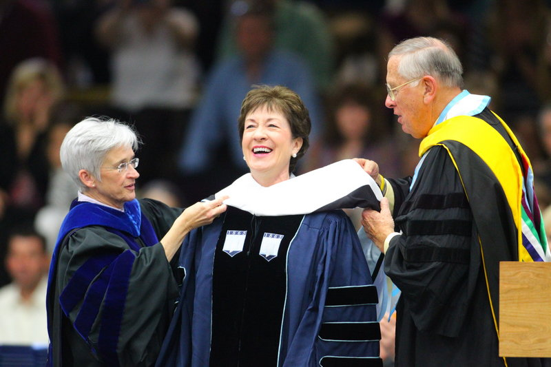 University of Maine Provost Susan Hunter, left, and Trustee William Johnson, right, confer an honorary doctorate upon U.S. Sen. Susan Collins at commencement ceremonies Saturday in Orono. In her address, Collins encouraged graduates to