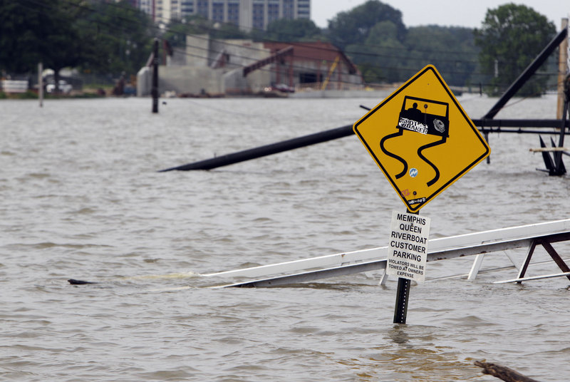 A ramp leading to the Memphis Queen riverboat and its parking area are under water Saturday in Memphis, Tenn.