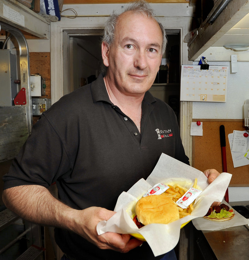 Mike Roylos shows off a Falafal Burger Basket at Spartan Grill and Coffee.