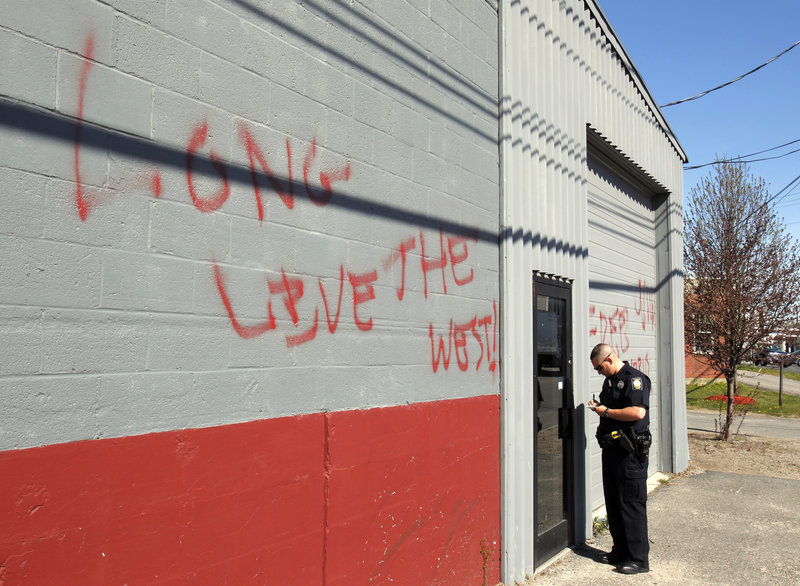 "A police officer checks out the Maine Muslim Community Center May 2 after the mosque was spray-painted with graffiti in the wake of Osama bin Laden's death. The writing says, ""Osama today Islam tomorow (sic),"" and ""Long live the West."""