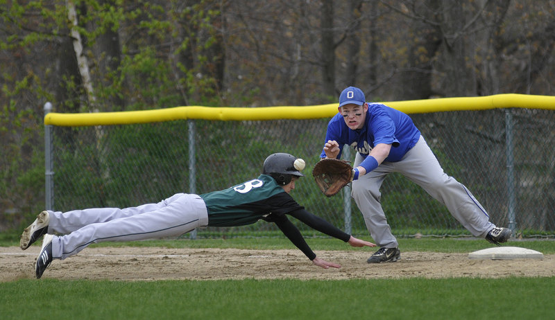 Joey Schnier of Waynflete dives safely back into first base as Jason Dutton of Old Orchard Beach fields the pickoff throw Monday in Portland. Waynflete won, 6-4.
