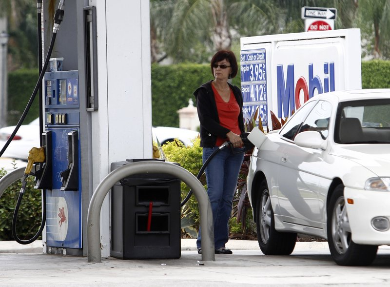 A motorist fills her gas tank at a Mobil gas station in Pembroke Pines, Fla., where the price of regular gas was near $4 a gallon last week. Retail gas prices are not falling immediately, despite the sharp drop in the cost of crude oil.