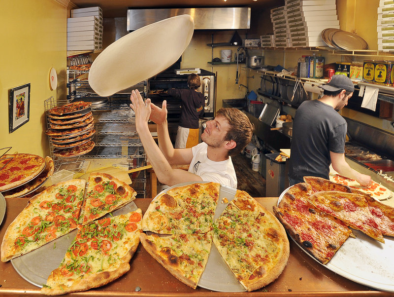 At Otto pizza in Portland, Travis Curran tosses pizza dough Tuesday while Nick Belkas adds the special eclectic toppings that attracted the attention of the Food Network. In the background, Jillian Smitherman attends to the ovens as the night crew works hard to keep up with the dinner demand.