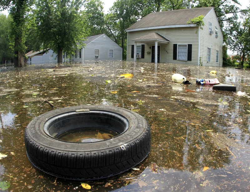 A tire and other debris floats by flooded homes in Memphis. As the floodwaters headed south, the river level was expected to hold just below 48 feet in Memphis.