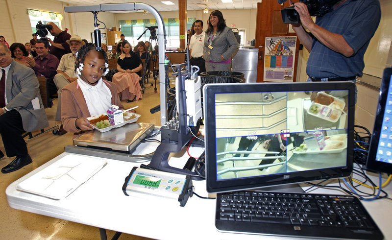 At White Elementary School in San Antonio, third-graderAlexis Brooks places her plate on the return tray as digitalfood-analysis equipment is demonstrated Wednesday. Health officials are studying nutrition among students at five schools.