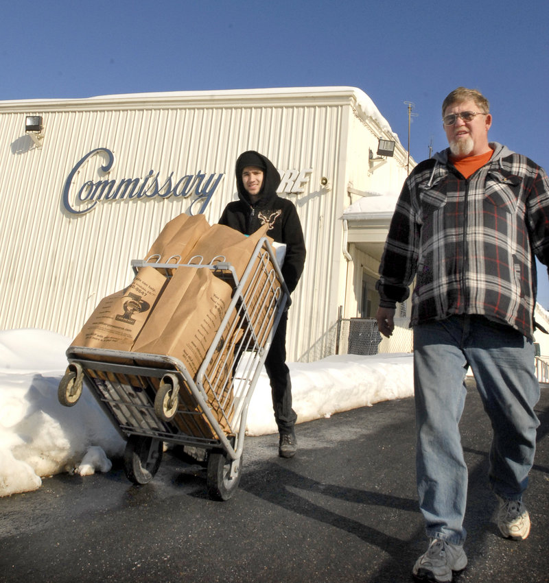 Commissary worker Michael Cholewinski pushes a cart loaded with groceries for Robin Spears of Skowhegan in 2009. The Topsham facility is due to close sometime after Sept. 15, but Mainers in Congress are seeking a reprieve.