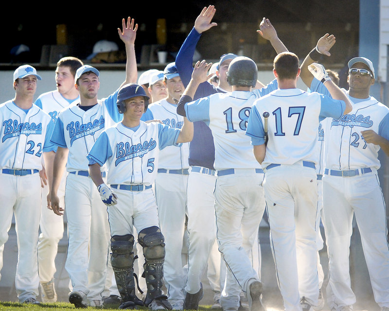 Jake Gardiner, 18, and Zach Gardiner, 17, are welcomed by their Westbrook teammates after scoring on a double by Sam Stauble in the second inning of the 7-0 victory against Marshwood at Olmsted Field.