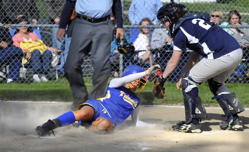 Jessie L'Heureux of Falmouth slides into the plate in the fifth inning in front of Yarmouth catcher Julie Dursema during their Western Maine Conference softball game at Falmouth. L'Heureux also had a run-scoring triple during a 4-3 victory.