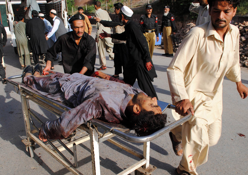 Rescuers rush a wounded man to a Peshawar hospital Friday after suicide bombers staged the bloodiest attack in Pakistan since a U.S. raid killed al-Qaida leader Osama bin Laden.