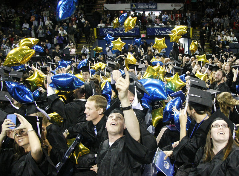 Graduates look up as they are showered with balloons at the closing of the University of Southern Maine's 131st commencement at the Cumberland County Civic Center in Portland on Saturday.